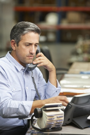 dispatcher: Manager Working At Desk In Warehouse