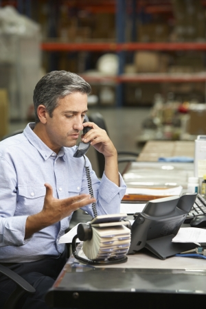 rolodex: Manager Working At Desk In Warehouse