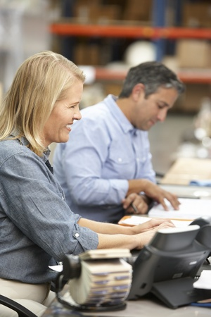 rolodex: Business Colleagues Working At Desk In Warehouse Stock Photo