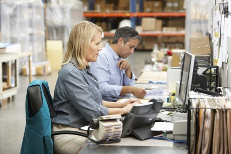 small: Business Colleagues Working At Desk In Warehouse Stock Photo