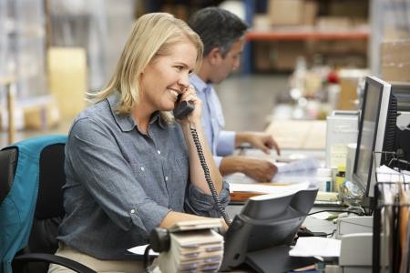 Femme d'affaires travaillant à son bureau dans l'entrepôt Banque d'images