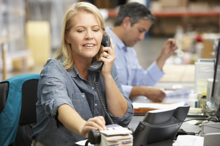 Businesswoman Working At Desk In Warehouse photo