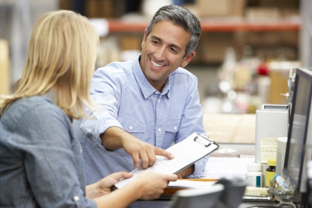 business management: Business Colleagues Working At Desk In Warehouse Stock Photo