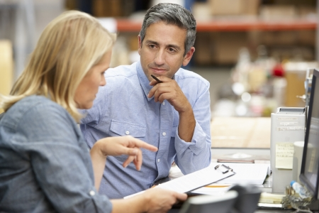 dos personas hablando: Colegas de negocios que trabajan en el escritorio en almacén Foto de archivo