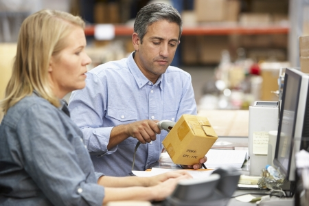 warehouse worker: Business Colleagues Working At Desk In Warehouse Stock Photo