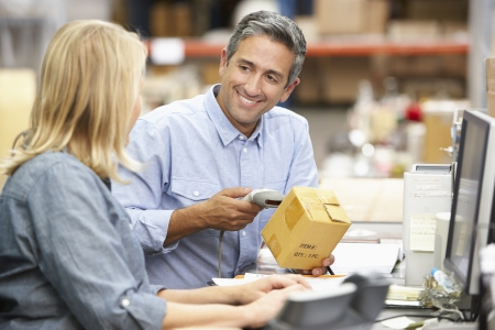 barcode scanner: Business Colleagues Working At Desk In Warehouse Stock Photo