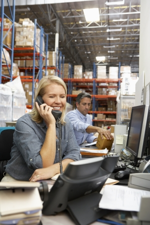 Businesswoman Working At Desk In Warehouse Stock Photo - 19530615