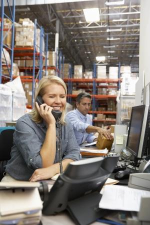 warehouse worker: Businesswoman Working At Desk In Warehouse