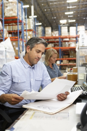 business owner: Business Colleagues Working At Desk In Warehouse Stock Photo