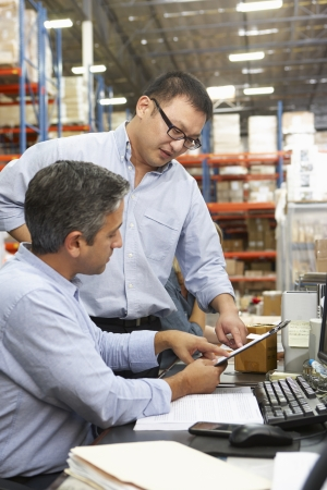 small business: Business Colleagues Working At Desk In Warehouse Stock Photo