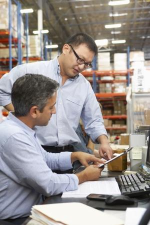 dos personas platicando: Colegas de negocios que trabajan en el escritorio en almac?n