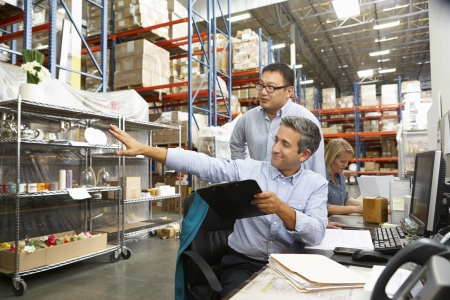 order shipment: Business Colleagues Working At Desk In Warehouse Stock Photo