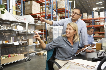 three shelves: Business Colleagues Working At Desk In Warehouse Stock Photo