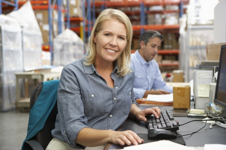small business owner: Businesswoman Working At Desk In Warehouse