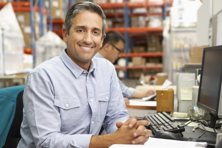 Businessman Working At Desk In Warehouse photo