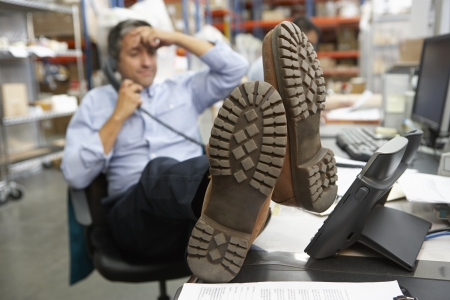 Businessman Putting Feet Up On Desk In Warehouse Stock Photo - 19530393