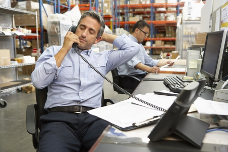 small business owner: Businessman Working At Desk In Warehouse