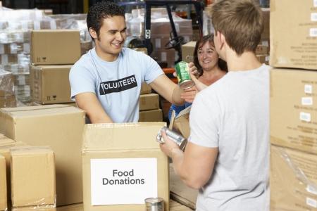 Volontaires collectant des dons de nourriture dans un entrepôt Banque d'images - 85400975