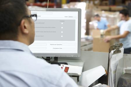 Personne au terminal d'ordinateur dans l'entrepôt de distribution Banque d'images