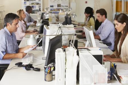 忙しいオフィスでデスクで作業チーム 写真素材