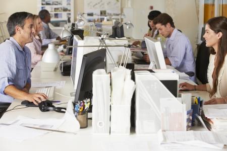 trabajador oficina: El equipo de trabajo en el escritorio en la oficina ocupada