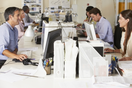 people at work: Team Working At Desks In Busy Office