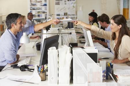ležérní: Tým pracuje na pulty v rušné kanceláři Reklamní fotografie