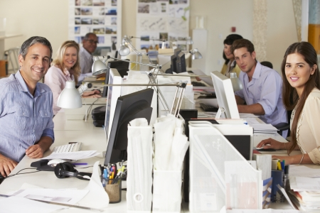 Team Working At Desks In Busy Office photo