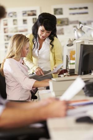 trabajando: Dos mujeres que trabajan en escritorio en la Oficina de Creative Busy