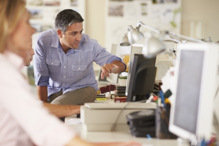 casual meeting: Workers At Desks In Busy Creative Office Stock Photo