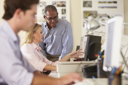 female office worker: Workers At Desks In Busy Creative Office Stock Photo