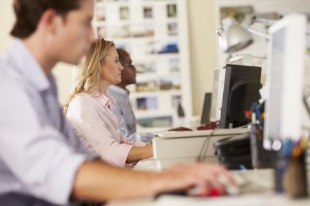 忙しいクリエイティブ ・ オフィスのデスクで労働者