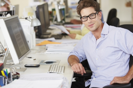studio: Man Working At Desk In Busy Creative Office Stock Photo