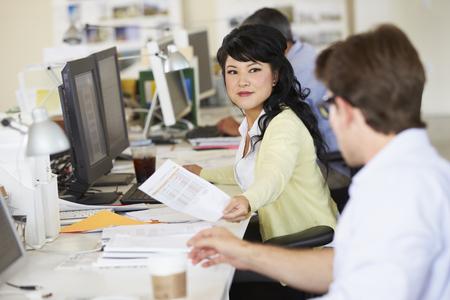 empleado de oficina: Mujer que trabaja en el escritorio en la oficina creativa Busy Foto de archivo