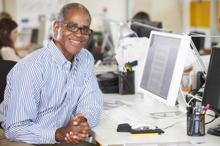 african businessman: Man Working At Desk In Busy Creative Office Stock Photo