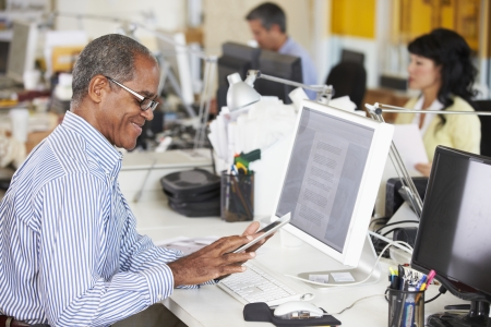 Man Using Digital Tablet In Busy Creative Office photo