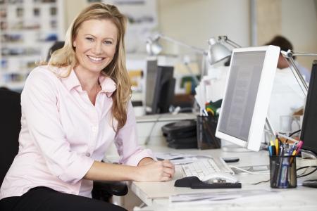 trabajador oficina: Mujer que trabaja en el escritorio en la oficina creativa Busy Foto de archivo