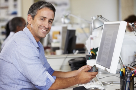 mobile office: Man Using Mobile Phone At Desk In Busy Creative Office