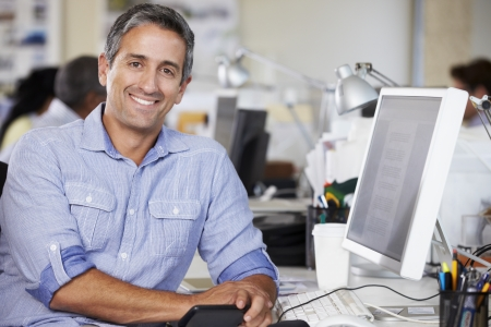 Man Working At Desk In Busy Creative Office Imagens