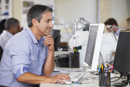 BUSY OFFICE: Man Working At Desk In Busy Creative Office Stock Photo