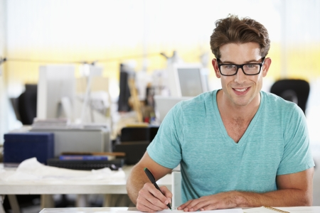 creative writing: Man Writing At Desk In Busy Creative Office Stock Photo
