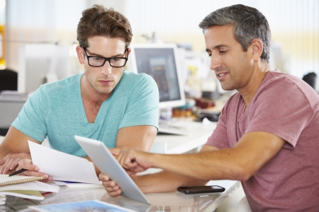 크리 에이 티브 사무실에서 태블릿 컴퓨터를 사용하는 두 남자 스톡 콘텐츠