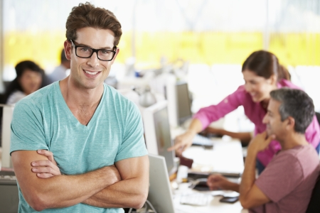 casual people: Portrait Of Man Standing In Busy Creative Office