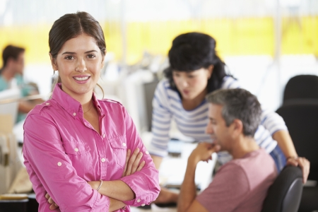 business background: Portrait Of Woman Standing In Busy Creative Office Stock Photo