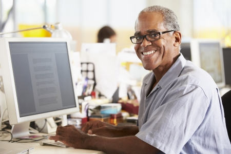 casual office: Man Working At Desk In Busy Creative Office Stock Photo