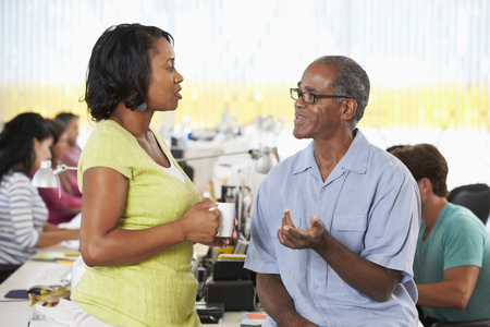 dos personas hablando: Trabajadores charlan en oficina creativa Busy Foto de archivo