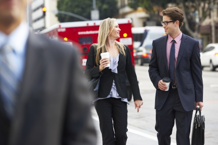 Businessman And Businesswoman In Street With Takeaway Coffee photo