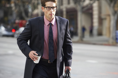 Businessman Hurrying Along Street Holding Takeaway Coffee photo