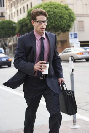 hurrying: Businessman Hurrying Along Street Holding Takeaway Coffee