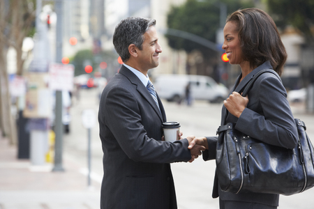 Businessman And Businesswoman Shaking Hands In Street Stock Photo - 23128858